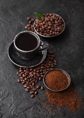 Cup of fresh raw organic coffee with beans and ground powder with cane sugar cubes with coffee tree leaf on dark background. Black ceramic mug Фото со стока