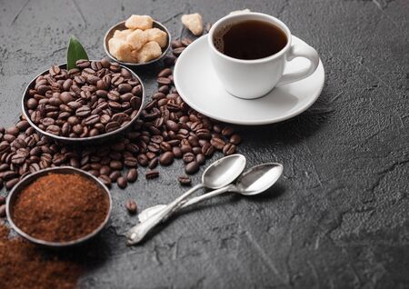 White cup of fresh raw organic coffee with beans and ground powder with cane sugar cubes with coffee tree leaf on dark background. Top view