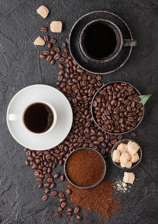 Black and white cups of fresh raw organic coffee with beans and ground powder with cane sugar cubes with coffee tree leaf on black background.