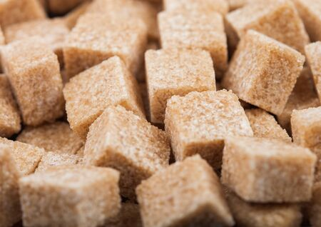 Close-Up shot of natural brown sugar cubes on white.