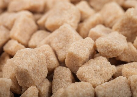 Close-Up shot of natural brown unrefined sugar cubes on white.