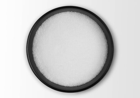 Black bowl of natural white refined sugar on white. Top view