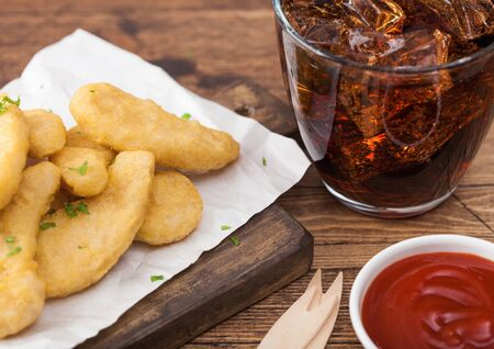 Buttered chicken nuggets on chopping board with glass of cola and ketchup on wood background. Фото со стока