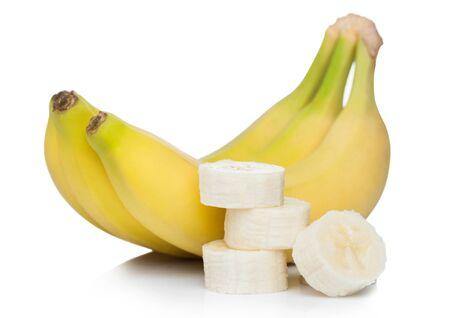 Verse rijpe biologische bananen cluster met gesneden stukjes op wit. Stockfoto