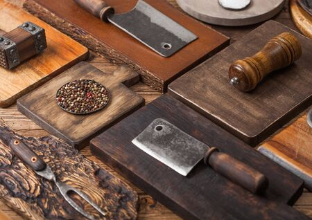 Different sizes and shapes kitchen chopping boards on wooden background with meat hatchets, fork and knife and other utensils.