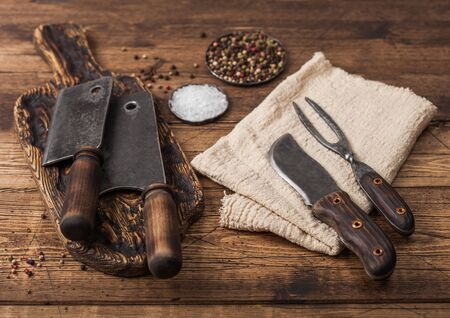 Vintage hatchets for meat on wooden chopping board with salt and pepper on wooden background with linen towel and fork and knife.