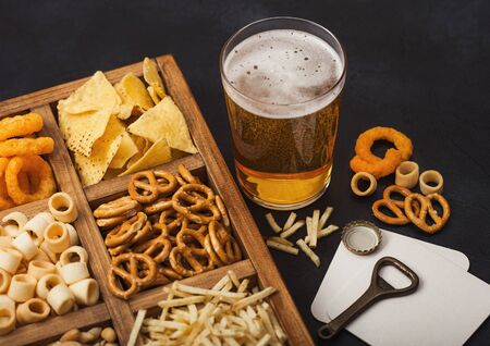 Glass of craft lager beer and opener with box of snacks on dark background. Pretzel,salty potato sticks, peanuts, onion rings with nachos in vintage box with openers and beer mats. Top view Stock fotó