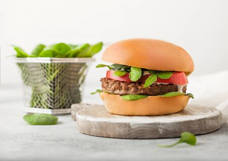 Healthy vegetarian meat free burger on round chopping board with vegetables and spinach on light background.