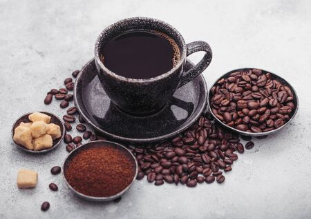 Cup of fresh raw organic coffee with beans and ground powder with cane sugar cubes with coffee tree leaf on light background. Stockfoto