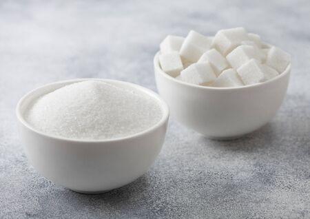 Platos de tazón blanco de terrones de azúcar blanco natural y azúcar refinada sobre fondo claro. Vista superior