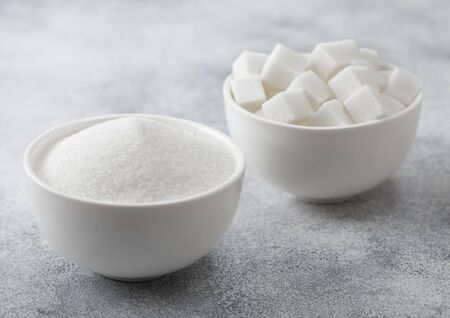 White bowl plates of natural white sugar cubes and refined sugar on light background. Top view