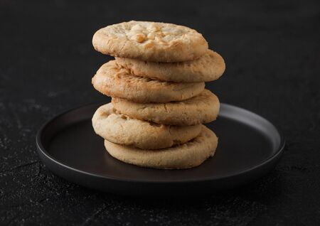 White chocolate biscuit cookies on black ceramic plate on black table background.