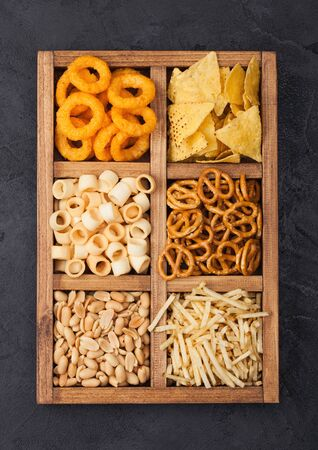 Various snacks in vintage wooden box on black kitchen background. Onion rings,nachos, salty peanuts with potato sticks and pretzels. Suitable for beer and fizzy drinks.  Stock fotó