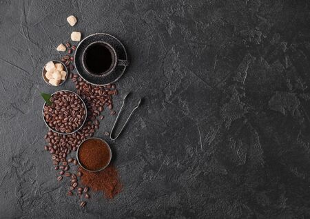 Cup of fresh raw organic coffee with beans and ground powder with cane sugar cubes with coffee tree leaf on dark background.