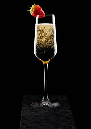Elegant glass of yellow champagne with strawberry on top on black marble board on black.