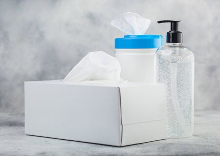 Plastic container with alcohol wipes with hand sanitizer plastic container and box of tissues on white background. Best protection from all viruses.