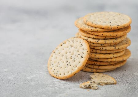 Stack of various organic crispy wheat flatbread crackers with sesame and salt on light background.