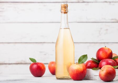 Bottle of homemade organic apple cider with fresh apples in box on wooden background, Glass with ice cubes