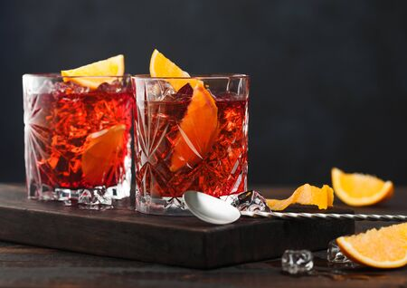 Negroni cocktail in crystal glasses with orange slice and fresh raw oranges on chopping board with spoon on wooden background.