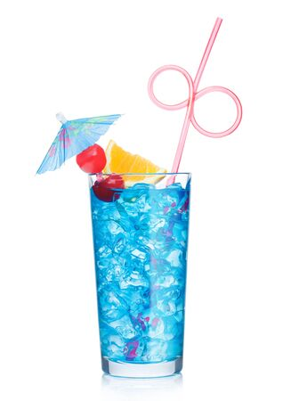 Blue lagoon cocktail highball glass with straw and orange slice with sweet cherry and umbrella on white background. Vodka and blue curacao liqueur mix.