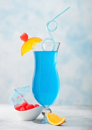 summer cocktail in classic glass with sweet cocktail cherries and orange slice with umbrella on blue table background. Archivio Fotografico