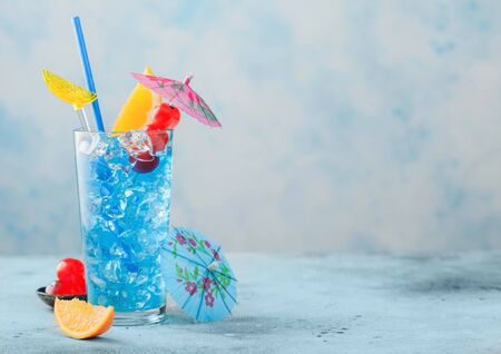 summer cocktail in highball glass with sweet cocktail cherries and orange slice with umbrella on blue table background. Space for text