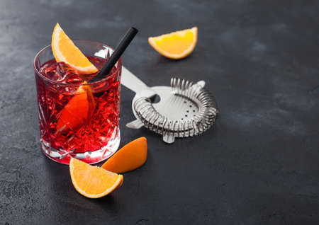 Negroni cocktail in crystal glass with orange slice and fresh raw oranges with strainer on black background. Top view
