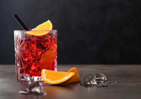 Negroni cocktail in crystal glass with orange slice and black straw on brown table background. Space for text