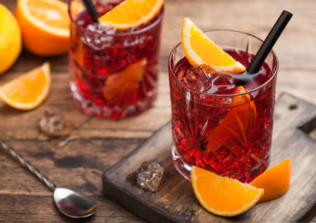 Negroni cocktail in crystal glasses with orange slice and fresh raw oranges on chopping board with strainer on wood background. Top view
