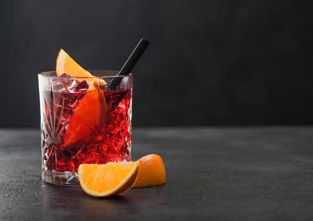 Negroni cocktail in crystal glass with orange slice and black straw on black table background. Stock fotó