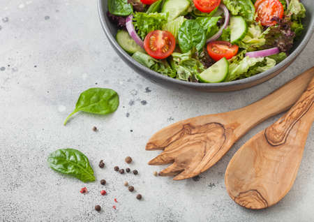 Gray bowl with healthy fresh vegetables salad with lettuce and tomatoes, red onion and spinach on light table background with spatula spoon and fork. Top view Stock fotó