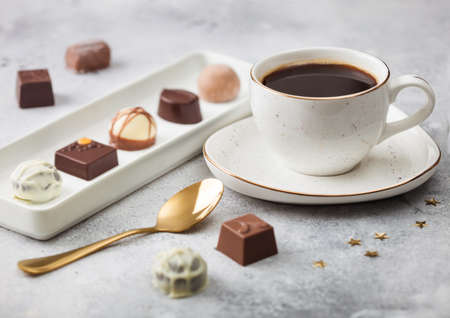 Luxury Chocolate candies in white porcelain plate with cup of black coffee and golden spoon on light background. Stock fotó