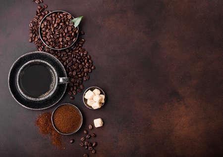 Cup of fresh raw organic coffee with beans and ground powder with cane sugar cubes with coffee tree leaf on dark background. Black ceramic mug 版權商用圖片