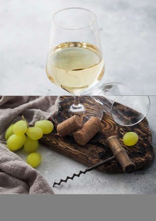Glass of white homemade wine with corks, corkscrew and grapes on wooden board with linen cloth on light table background. Top view