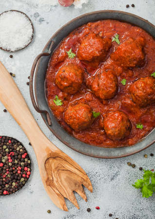 Meatballs in tomato sauce with pepper, garlic and parsley on light table with utensils. Top view