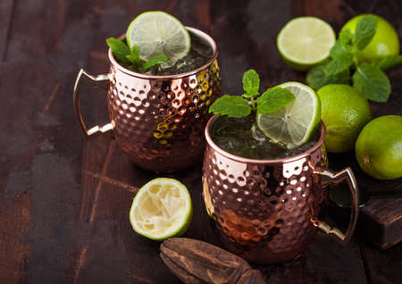 Moscow mule cocktail in a copper mug with lime and mint and wooden squeezer on dark wooden table background. Space for text