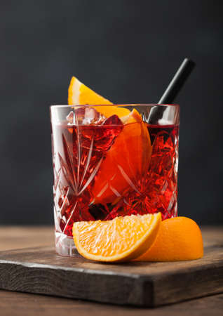 Negroni cocktail in crystal glass with orange slice and black straw on chopping board on wood background. Macro