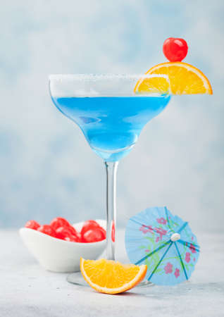Blue lagoon summer cocktail in margarita glass with sweet cocktail cherries and orange slice with umbrella on blue table background.