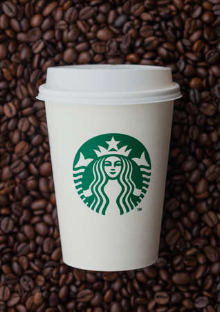 LONDON, UK - SEPTEMBER 09, 2020: Paper cup for takeaway of Starbucks coffee on top of fresh raw coffee beans.