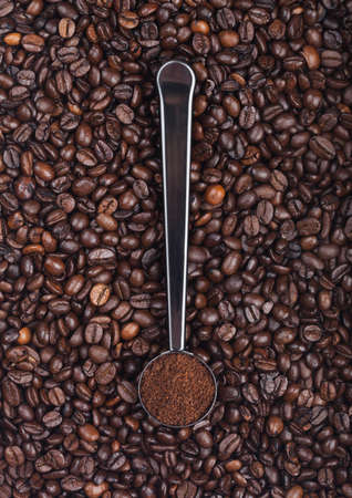 Fresh raw organic coffee powder in silver steel scoop on top of coffee beans. Top view Stock fotó