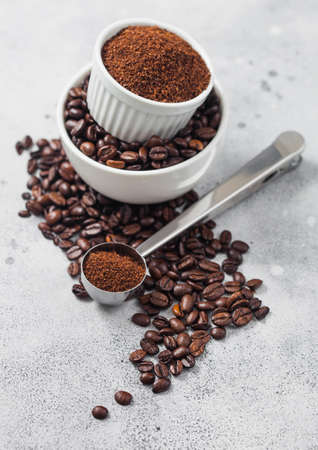Fresh raw organic coffee beans in white bowl and powder on ligh table background and round steel scoop.
