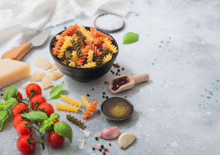 Fusilli pasta in black bowl with parmesan cheese and tomatoes, oil and garlic with basil and linen towel on light background. Space for text