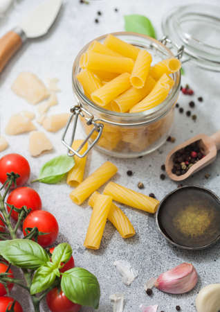 Fresh raw penne pasta in glass jar with tomatoes and basil, garlic and oil with parmesan cheese and salt and pepper on light background.Top view 版權商用圖片