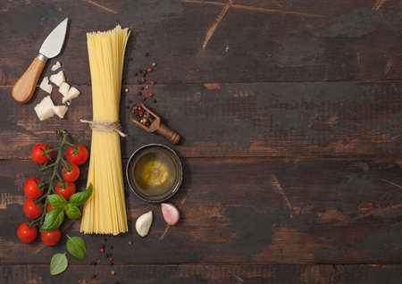 Raw spaghetti with cherry tomatoes and basil, garlic and oil with parmesan cheese and salt and pepper on wooden background. Space for text