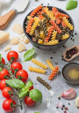 Fresh raw tricolore fusilli pasta in black bowl with cherry tomatoes and basil, garlic and oil with parmesan cheese on light table background.