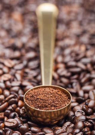 Ground coffee in golden steel scoop on fresh coffee beans background. Macro