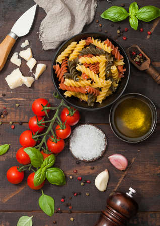 Fusilli pasta in black bowl with parmesan cheese and tomatoes, oil and garlic with basil and linen towel on wooden background. Top view 版權商用圖片