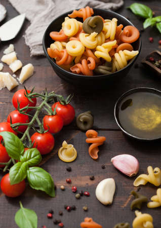 Fresh raw tricolore trottole pasta in black bowl with cherry tomatoes and basil, garlic and oil with parmesan cheese on wooden background. Top view