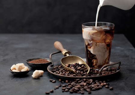 Pouring fresh milk into glass of iced black coffee on tray with beans and ground coffee with cane sugar and vintage shop on black background. Space for text