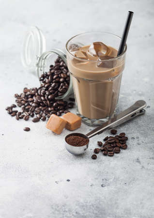 Glass of iced coffee with milk with jar of coffee beans and salted caramel and silver scoop on light table background. Zdjęcie Seryjne